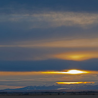 A winter sunset glows over the Rock Mountains and Gallatin Valley near Belgrade, Montana.