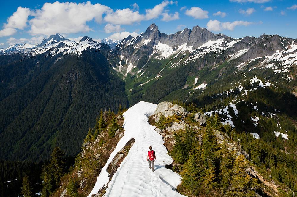 Ian Derrington hikes the summit ridge of Damnation Peak towards Mount Triumph, North Cascades National Park, Washington.
