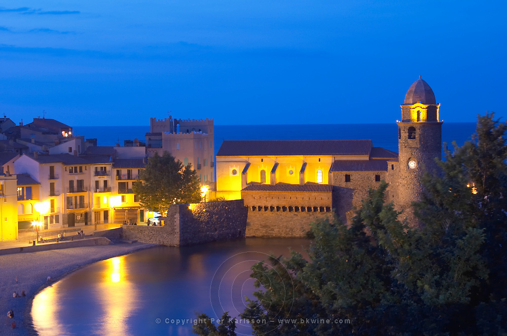 The church Eglise Notre Dame des Anges, our lady of the angels. With its emblematic church tower. The beach in the village. Collioure. Roussillon. France. Europe. In the evening with illumination and street lights.