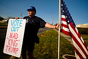 "14 OCTOBER 2020 - DES MOINES, IOWA: A man who identified himself as a ""Patriotic American"" picketed the entrance of the Des Moines International Airport, where President Donald Trump spoke at a campaign rally. About 10,000 people were expected to attend the rally. Trump spoke at the rally, despite testing positive for COVID-19 less than three weeks ago. The rally did not meet the CDC guidelines for a safe gathering in the time of Coronavirus.        PHOTO BY JACK KURTZ"