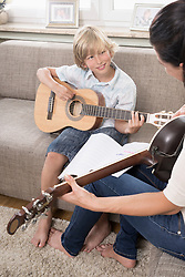 Woman with her son playing guitar in living room, Bavaria, Germany
