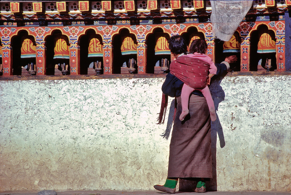 A woman with a child on her back spins prayer wheels along a wall at Paro Dzong in Bhutan.