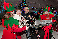 Councilor Brenda Baer and Laconia Police Chief Chris Adams  take a ride in Santa's sleigh as they enter the magical Christmas Village during opening night Thursday evening.  (Karen Bobotas/for the Laconia Daily Sun)