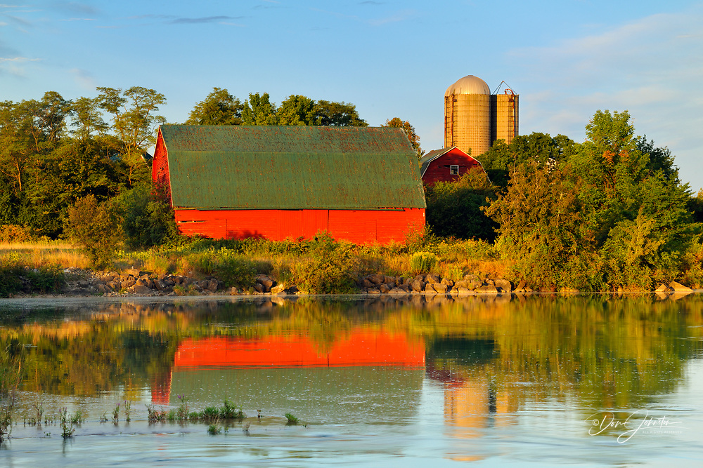 An aging red barn reflected into Gibson Lake waterway (hydro controlled) at dawn, Thorold, Ontario, Canada