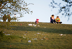 © Licensed to London News Pictures. 18/04/2021. London, UK. Litter remans strewn across the top of Primrose Hill in North London, despite the park being closed from 10pm last night. A curfew has been put in to place at the park over the weekend  to prevent large gatherings in the evening. Photo credit: Ben Cawthra/LNP