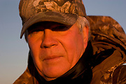 Hunter Byron Grubb duck hunting at dawn on a hilltop south-east of Minot. The duck hunters travel in the dark to the place they suspect will be the morning feeding roost for ducks. As the sun comes up they have prepared decoys in the field and hide behind some undergrowth in their camouflage clothing. As the sun rises soem ducks take to the air for their morning feed. As they draw near the hunters make female and feeding duck calls to attract the flying birds towards the decoys and to within shooting range. The moment they are close enough the hunters quickly take aim anf fire their shotguns; some of the ducks fall to the ground. A great deal of work and effort goes into this type of shooting, with the result being a few fine Mallards for the pot.