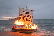 Ocean Rebellion staged a theatrical action with a Boris Johnson head and an Oilhead sitting in deckchairs on Marazion beach while a boat burns in the background on 5th June 2021 on Marazion beach, Cornwall, United Kingdom. The action was the part of an ongoing series of protests leading up to the G7 summit to be held nearby, featuring Boris Johnson sharing intimate quality-time in Cornwall with a Fossil Fuel Buddy. The celebrity pair were seen sitting on deck-chairs as the sun rose and a boat burned in the bay, billowing black smoke, across its sail inscribed 'Your Children's Future.' The G7 delegates will be staying at the Tregenna Castle Hotel for the upcoming summit which will be held in Carbis Bay between June 11-13. The theatrical protesters were calling out British politics involvement with the fossil fuel industry. The summit will see world leaders gather to discuss some of the most pressing challenges facing us, from climate change to tackling the ongoing Covid-19 pandemic.
