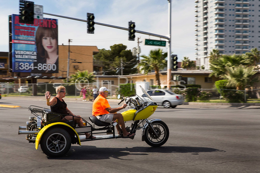 Elderly couple on 3 wheel motocycle downtown Las Vegas. In Nevada you need neither license nor helmets for a 3 wheeler.