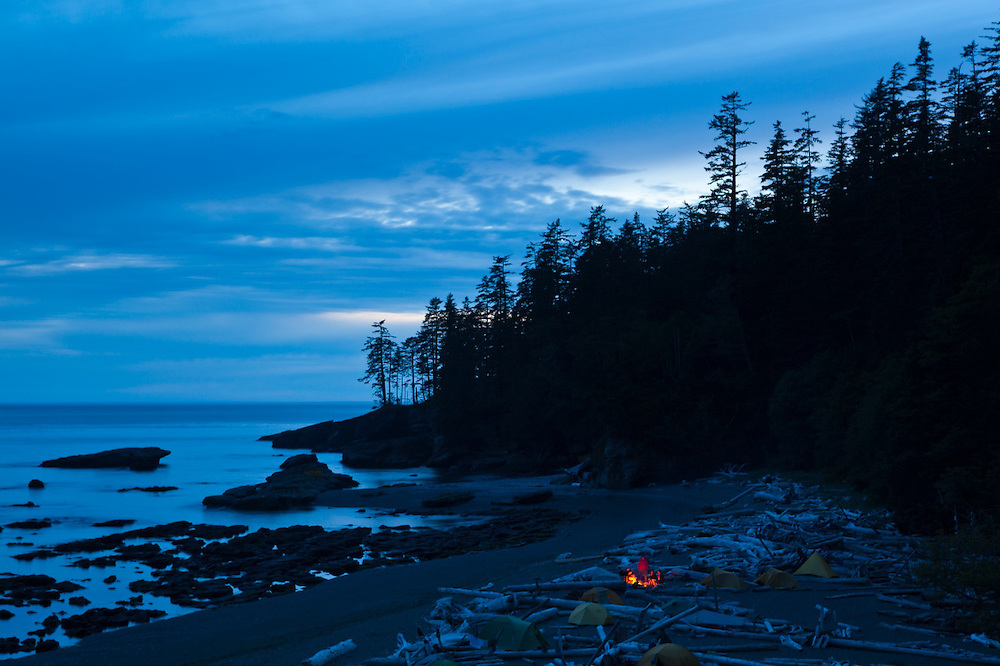 Hikers keep warm by a campfire at dusk on Tsusiat Beach, West Coast Trail, British Columbia, Canada.