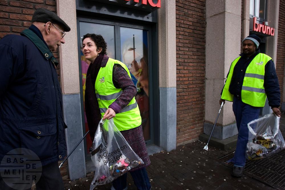Samen met enkele raadsleden van GroenLinks uit Nijmegen en mensen van Stichting Dagloon, ruimt partijleider Femke Halsema zwerfvuil op bij het station van Nijmegen als onderdeel van de campagne voor de gemeenteraadsverkiezingen op 7 maart.<br /> <br /> Party leader Femke Halsema of GroenLinks is cleaning up the mess nearby the train station of Nijmegen with homeless people as part of the campaign for local elections.