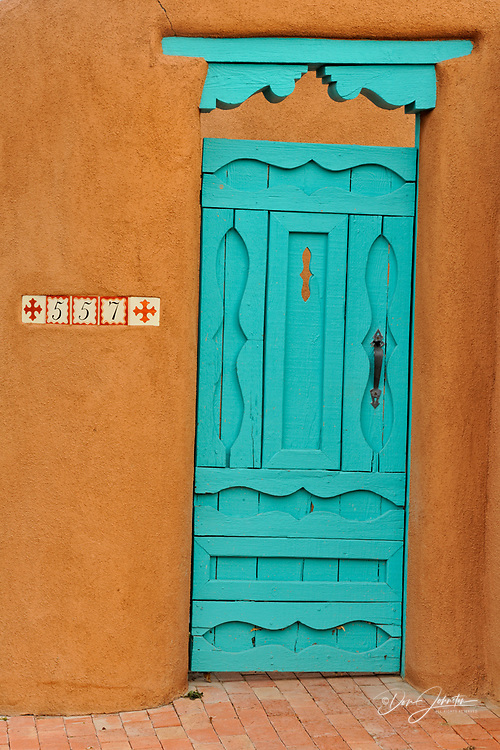 Adobe wall details, with painted door in residential Santa Fe, Santa Fe, New Mexico, USA