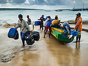 18 JULY 2016 - KUTA, BALI, INDONESIA:  Fishermen land their small outrigger canoe at Pasar Ikan pantai Kedonganan, a fishing pier and market in Kuta, Bali.   PHOTO BY JACK KURTZ