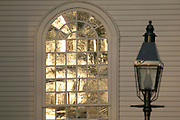 Newport, RI 2006 - Gas lamp with sunset reflecting in arched window of colonial Trinity church