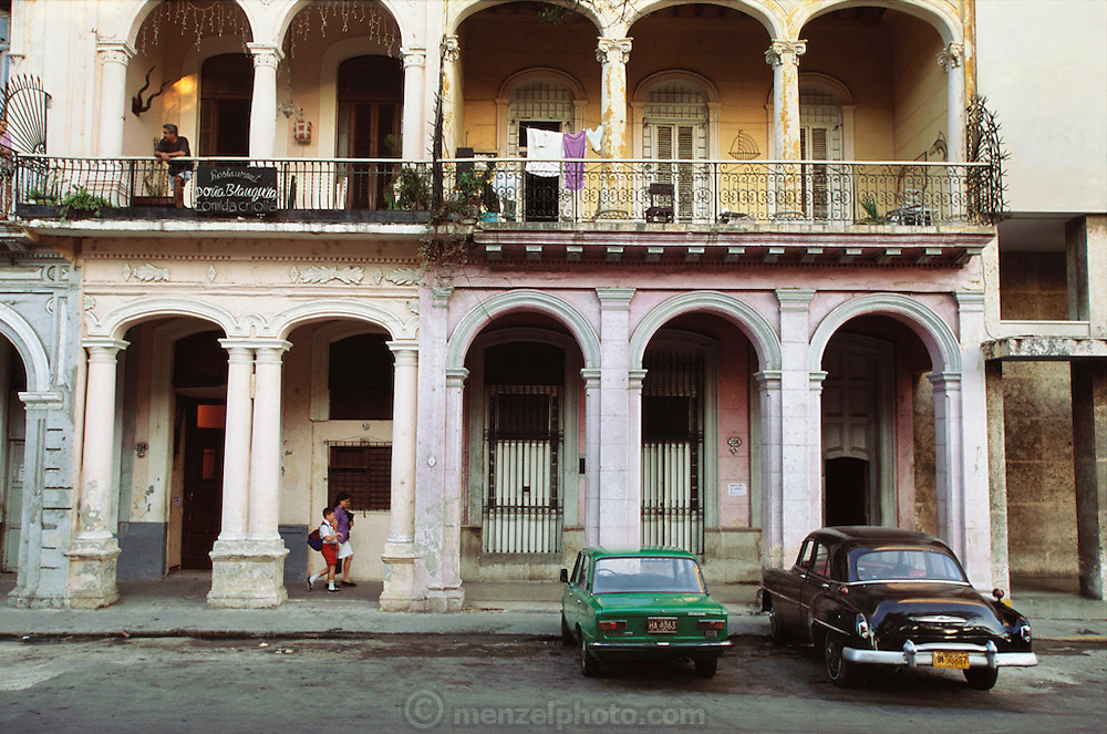 Children walk to school under colonial archways, and past fifties-era American cars, in downtown Havana, Cuba.