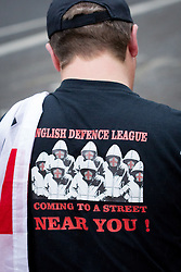"© Licensed to London News Pictures . 12/10/2013 . Bradford , UK . An EDL supporter wearing a t shirt reading "" English Defence League coming to s a street near you "" . The EDL hold a demonstration in Bradford today (Saturday 12th October 2013) . It is their first demonstration since leaders Stephen Yaxley-Lennon (aka Tommy Robinson ) and Kevin Carroll quit . Approximately 500 protesters gathered near the city centre . Photo credit : Joel Goodman/LNP"