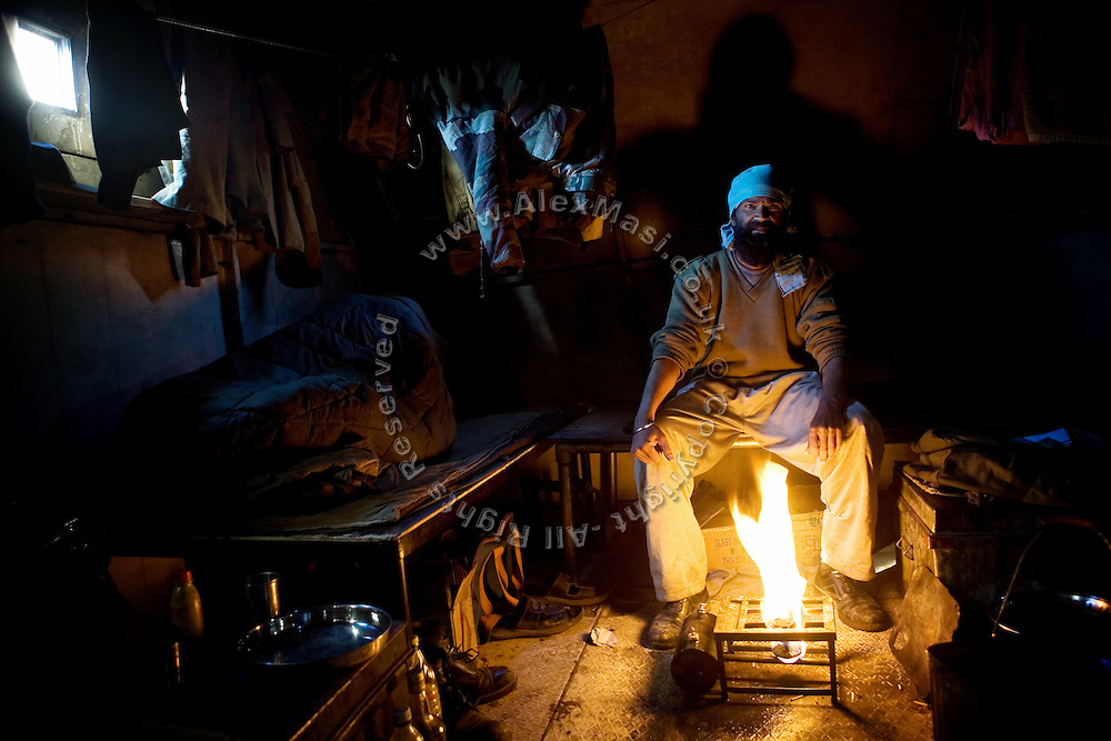 An Indian serviceman is photographed while warming up in his temporary room on the Leh-Manali Highway where he supervises labourers.