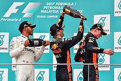 SEPANG, Oct. 1, 2017  Mercedes driver Lewis Hamilton (L) of Britain and Red Bull driver Daniel Ricciardo (C) of Australia pour champagne on Red Bull driver Max Verstappen of the Netherlands on the podium after the Formula One Malaysia Grand Prix at the Sepang Circuit in Malaysia, on Oct. 1, 2017. Max Verstappen claimed the title of the event. (Credit Image: © Chong Voon Chung/Xinhua via ZUMA Wire)