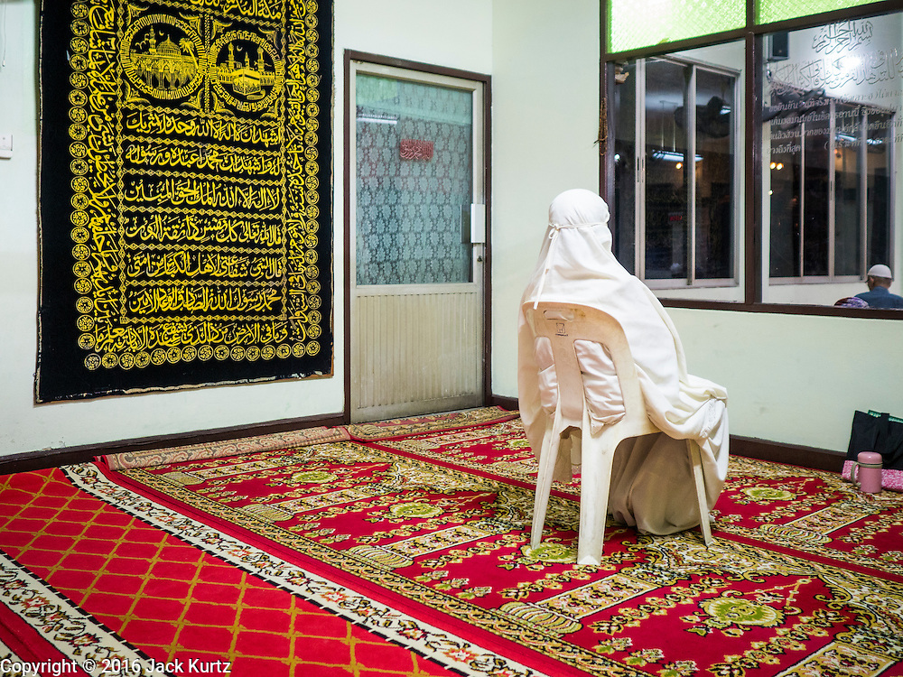 05 JUNE 2016 - BANGKOK, THAILAND:  The only woman at evening prayers in the women's prayer room at Masjid Darul Faha, a small mosque in the Muslim majority neighborhood of Ban Krua in Bangkok on the night before the start of Ramadan. Ramadan is the ninth month of the Islamic calendar, and starts on June 6 this year. It is observed by Muslims worldwide as a month of fasting to commemorate the first revelation of the Quran to Muhammad according to Islamic belief. This annual observance is regarded as one of the Five Pillars of Islam. Islam is the second largest religion in Thailand.       PHOTO BY JACK KURTZ