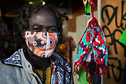 Dickson wearing one of his face masks during the second coronavirus national lockdownon on 7th of November 2020, East London, United Kingdom. Dickson has a small shop in Ridley Road Market and one of his many colorful items on sale are hand made face masks, made in Hackney. The UK Government introduced a 4 week lockdown from November 5th - December 2nd to combat the coronavirus outbreak. It is the third day of the national lockdown restrictions mean that people are only allowed to meet outside, in pairs and only if keeping social distance. Only if they already live together or have formed a social bubble can they interact freely.