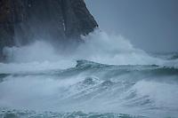 Large waves of winter storm crash against coastal cliffs at Unstad Beach, Vestvågøy, Lofoten Islands, Norway