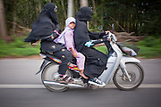 """Sept. 27, 2009 -- BACHO, THAILAND: Muslim Thai families use motorcycles for family transportation in Bacho, Narathiwat, Thailand. Thailand's three southern most provinces; Yala, Pattani and Narathiwat are often called """"restive"""" and a decades long Muslim insurgency has gained traction recently. Nearly 4,000 people have been killed since 2004. The three southern provinces are under emergency control and there are more than 60,000 Thai military, police and paramilitary militia forces trying to keep the peace battling insurgents who favor car bombs and assassination.   Photo by Jack Kurtz / ZUMA Press"""
