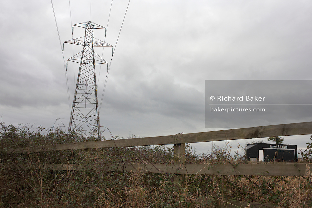 An electricity pylon stands against an overcast winter sky on rural land near Wrington, North Somerset England.