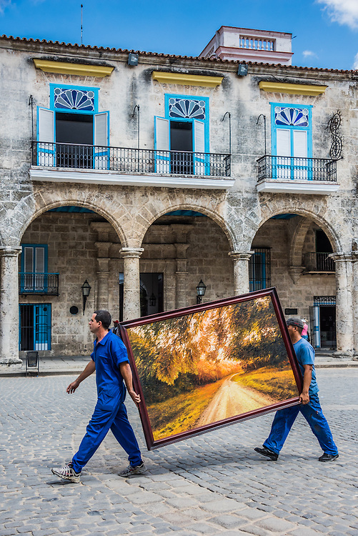 Two men transporting a painting in Havana, Cuba
