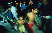 Two Roma brothers, Kosovo War refugees, pass through a gauntlet of police and customs guards after their arrival at Brindisi port, on the Italian coast, after traversing the Adriatic by Mafia boat. they are the luckier ones, as many Roma were drowned. They will be checked, processed and given Red Cross identity cards, and eventually able to seek a new life in Italy and Western Europe. Brindisi, Italy 1999