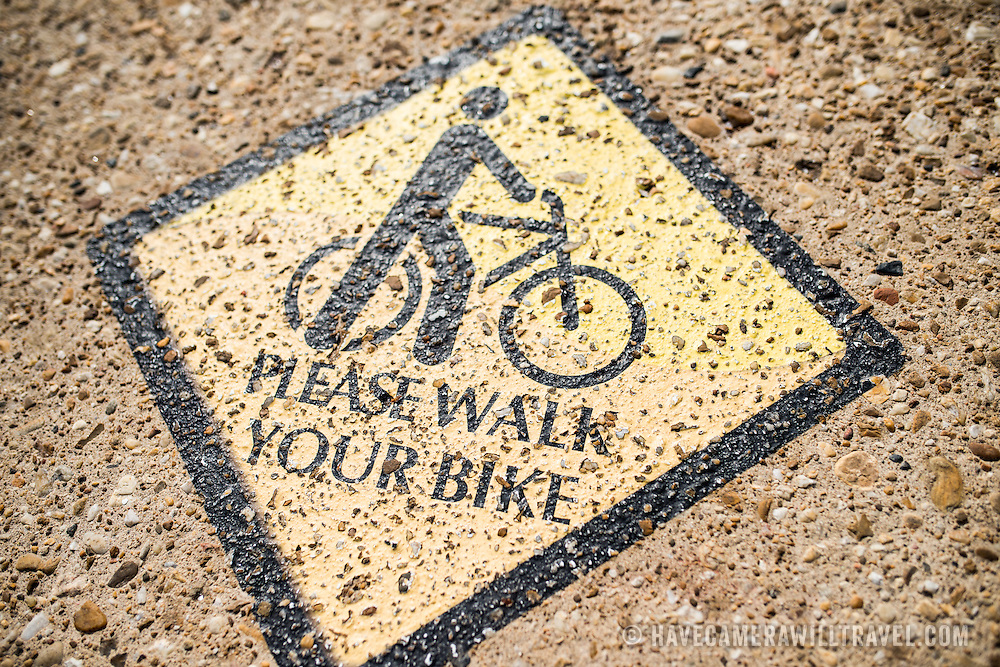 """A """"Please Walk Your Bike"""" caution sign pained on the sidewalk in Washington DC in an area that features heavy pedestrian traffic."""