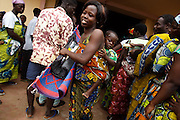 A woman carries a bundle containing items she was just given during a UNICEF-sponsored distribution session in Athieme, Benin  on Monday October 25, 2010. UNICEF donated water treatment tablets, mosquito nets and soap to affected families, while other partner organizations offered blankets, floormats, and buckets.