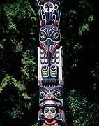 Killer Whale, Raven and Grizzly Bear over man's head figures on the Ga'akstalas Pole, carved by Wayne Alfred and Beau Dick in 1991 and based on a Kwakwaka'wakw design by Russell Smith.  Totem pole on display at Stanley Park, Vancouver, British Columbia, Canada.