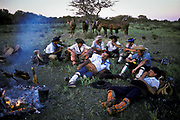 Gauchos drinking Maté tea (Yerba Maté) and eat a meal of barbecued meat around camp fire.