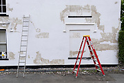 A ladder leans against a white wall, and red stepladders are positioned outside a home in need of fresh paint, in a rural English town, on 30th June 2021, in Aylsham, Norfolk, England.