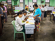 08 NOVEMBER 2015 - YANGON, MYANMAR:  A woman picks up her ballot at her polling place in central Yangon. The citizens of Myanmar went to the polls Sunday to vote in the most democratic elections since 1990. The National League for Democracy, (NLD) the party of Aung San Suu Kyi is widely expected to get the most votes in the election, but it is not certain if they will get enough votes to secure an outright victory. The polls opened at 6AM. In Yangon, some voters started lining up at 4AM and lines were reported to long in many polling stations in Myanmar's largest city.     PHOTO BY JACK KURTZ