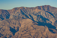 Telescope Peak and the Panamint Range glows in the early morning sunlight as seen from Dante's View. A fighter jet and a B-2 stealth bomber can be seen flying in front of the mountains.