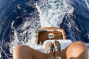 Photographers legs in the foreground of this wide angler view from the tuna tower looking down and a teak cockpit of a sportfishing boat trolling.