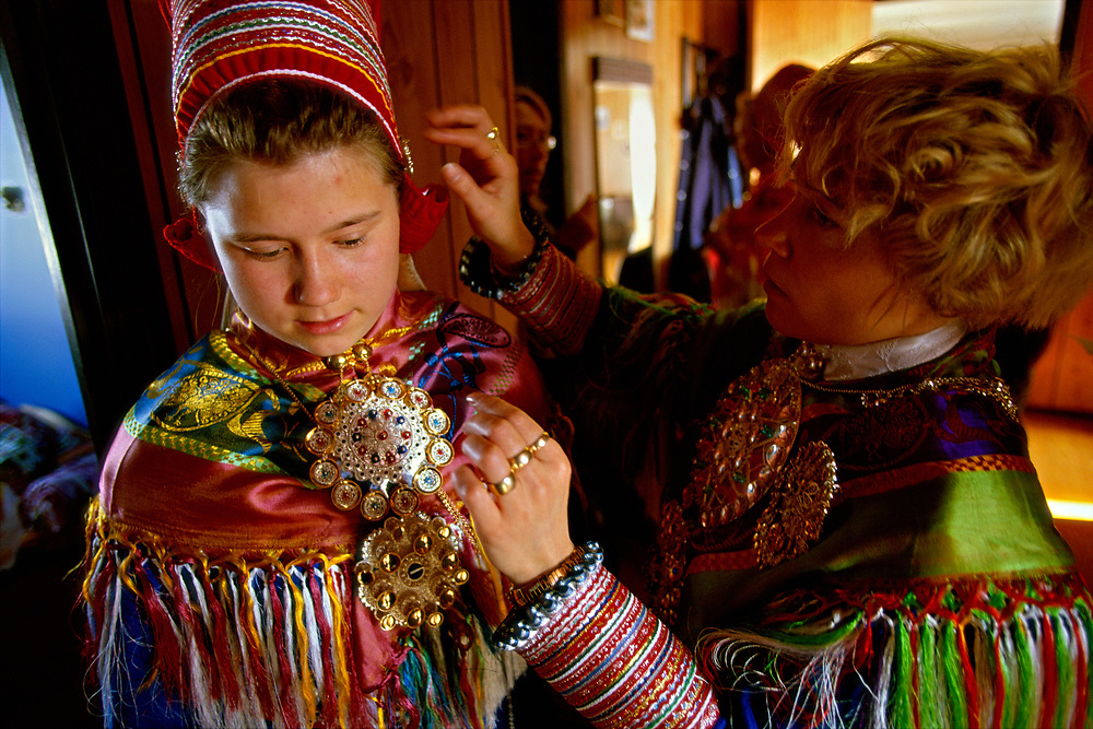 A Sami girl gets dressed in traditional clothes for her confirmation ceremony, Kautokeino, Norway. She is helped by her aunt, who adjusts the look of her hair. The Sami living in Kautokeino hold confirmations and other life cycle ceremonies at Easter time, after which the reindeer herders move with their herds to the Atlantic coast for summer pasture.  The traditional tunics that the Sami women wear are made of wool, the scarves of silk and the brooches holding the scarves together in front are made of silver.
