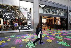 "© Licensed to London News Pictures. 25/11/2016. London, UK. A lone woman walks past the entrance to TOPSHOP on Oxford Street, London, shortly after opening on ""Black Friday"". Sales from this years Black Friday event are expected to top £2 billion. Photo credit: Tolga Akmen/LNP"