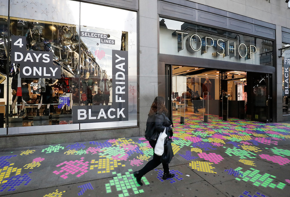 """© Licensed to London News Pictures. 25/11/2016. London, UK. A lone woman walks past the entrance to TOPSHOP on Oxford Street, London, shortly after opening on """"Black Friday"""". Sales from this years Black Friday event are expected to top £2 billion. Photo credit: Tolga Akmen/LNP"""