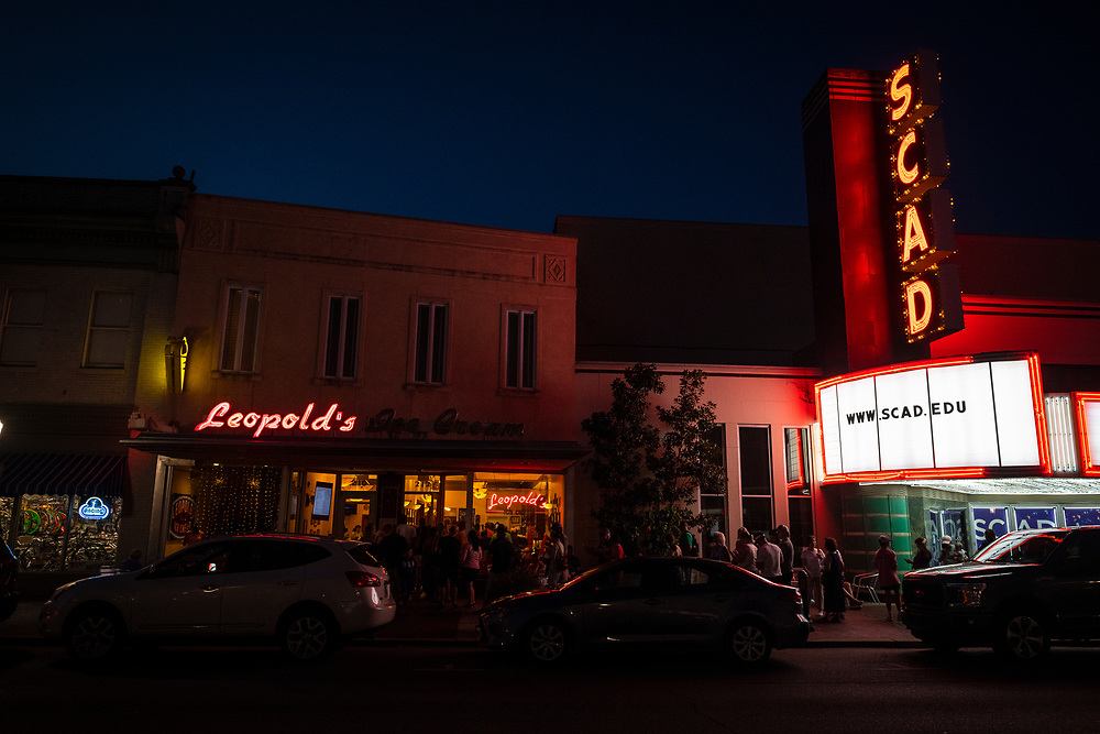 Savannah, Georgia - July 29, 2021: People stand in a long line on a summer night outside Leopold's ice cream store in downtown Savannah.