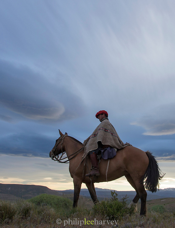 Gaucho on horseback overlooking the plains in twilight, Estancia Huechahue, Patagonia, Argentina, South America