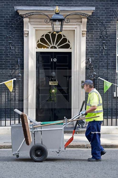 © London News Pictures. 04/09/2012. London, UK.  A council road cleaner cleaning dirt and rubbish from in front of Number 10 Downing Street on the day of cabinet reshuffle September 04, 2012. Photo credit: Ben Cawthra/LNP