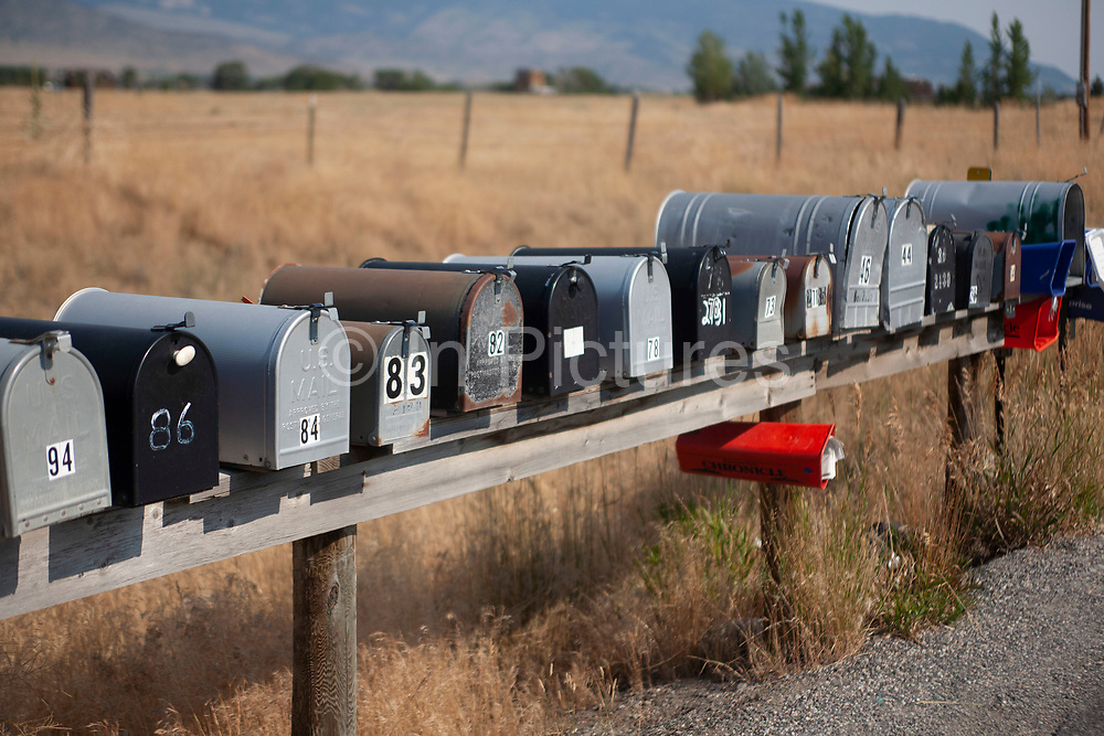 Line of postboxes at the entrance to properties in Paradise Valley on 6th August 2007 at Pray, near Livingstone, Montana. The fields are full of golden dried out summer grasses which match the yellow road markings.