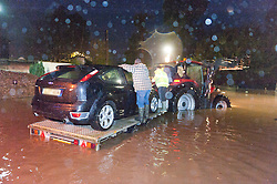 © Licensed to London News Pictures. 30/11/2015. Builth Wells, Powys, Wales, UK. Mid Wales farmers rescue one of their family whose car has been surrounded by flood waters. Large traffic jams on the A483 at Builth Wells are caused when the river Wye bursts it's banks and floods this busy road at rush hour. Photo credit: Graham M. Lawrence/LNP