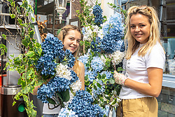 Licensed to London News Pictures. 24/06/2021. London, UK. Hannah Gardiner and Olesya Panova from Bloomsart flower displays prepare Wimbledon Village decorations ahead of the start of the Tennis Championships which is set to kick off this Monday (28 June 2021) for the first time in two years. The AELTC Championships at Wimbledon, southwest London is back on Monday after it was cancelled last year due to the Covid-19 pandemic. Capacity is down by 50% and fans must preordered tickets with no overnight queuing. Photo credit: Alex Lentati/LNP