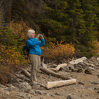 A photographer takes pictures beside Moraine Lake in Banff National Park, Alberta, Canada.