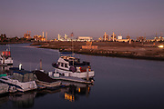 Marina in Los Cerritos Wetlands with oil refineries in the distance, Long Beach, california, USA