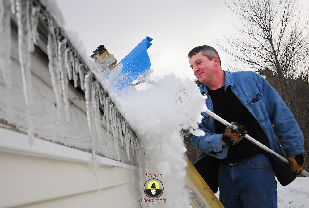 "1/31/09 -- BATH, Maine. Jon Wilson rakes snow and caked ice from the roof of his house in Bath in preparation for Tuesday's rainstorm. ""It hasn't been too bad this year, this is my first time so far. But, it's going to be pretty heavy this week with the rain.""  Photo by Roger S. Duncan."