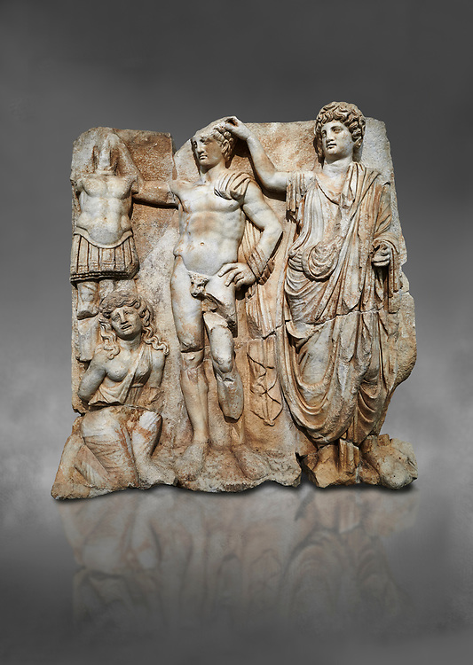 """Roman Sebasteion relief  sculpture of the Emperor and Roman People, Aphrodisias Museum, Aphrodisias, Turkey.  Against a grey background.<br /> <br /> The emperor is a naked warrior and is crowned by a personification of the Roman People or the Senate wearing a toga, the stately civilian dress of a Roman Citizen. The crown is an oak wreath, the corona civica or """"civic crown"""" awarded for saving citizens lives. The emperor is setting up a battlefield trophy beneath which kneels an anguished barbarian women captive .<br /> <br /> If you prefer to buy from our ALAMY STOCK LIBRARY page at https://www.alamy.com/portfolio/paul-williams-funkystock/greco-roman-sculptures.html . Type -    Aphrodisias     - into LOWER SEARCH WITHIN GALLERY box - Refine search by adding a subject, place, background colour, museum etc.<br /> <br /> Visit our ROMAN WORLD PHOTO COLLECTIONS for more photos to download or buy as wall art prints https://funkystock.photoshelter.com/gallery-collection/The-Romans-Art-Artefacts-Antiquities-Historic-Sites-Pictures-Images/C0000r2uLJJo9_s0"""
