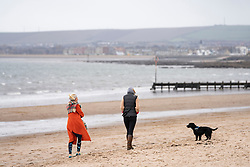 Portobello, Scotland, UK. 28 March, 2020. On the first weekend of the coronavirus lockdown the public were outdoors exercising and maintaining social distancing along Portobello beachfront promenade. Two females walking dog on beach.  Iain Masterton/Alamy Live News